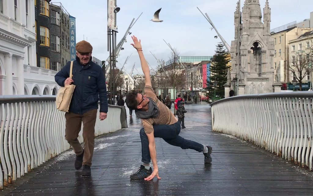 Stephen doing a yoga pose on a bridge in Cork, Ireland while an elderly man walks by.