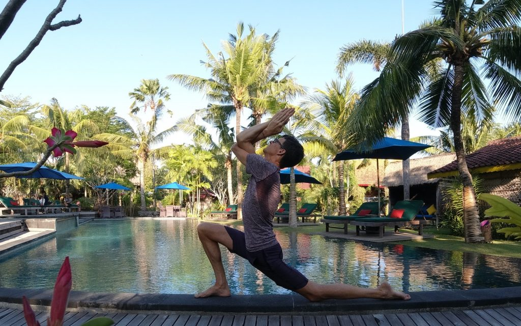 Stephen doing yoga by the pool at Desa Seni in Bali.