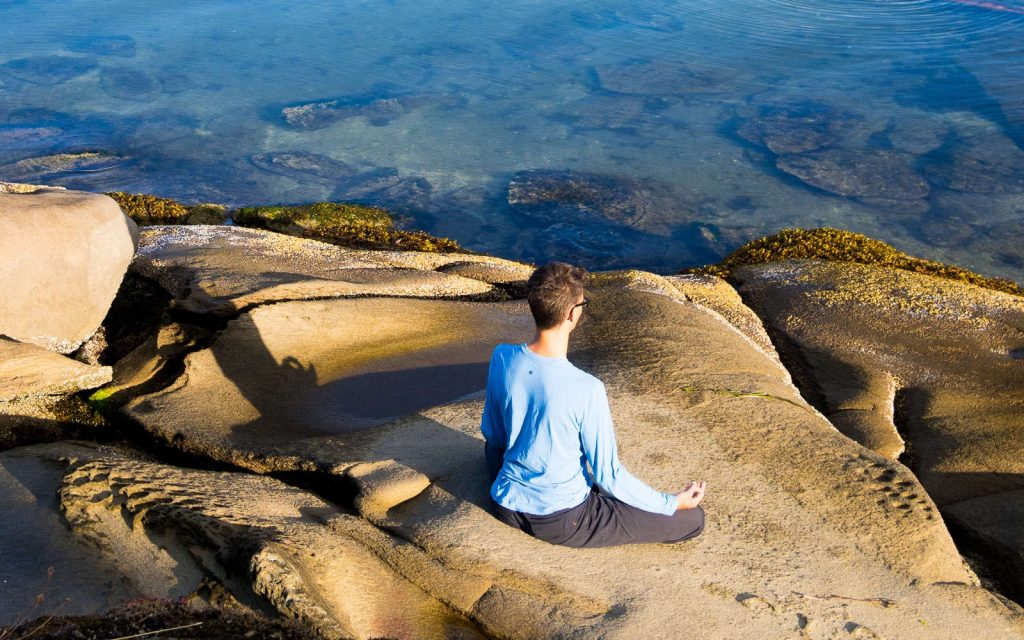 Stephen meditating on a rocky shore in BC in Canada.