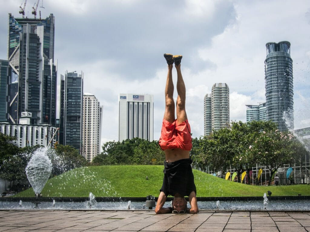 stephen doing headstand in kuala lumpur with skyscrapers in the background