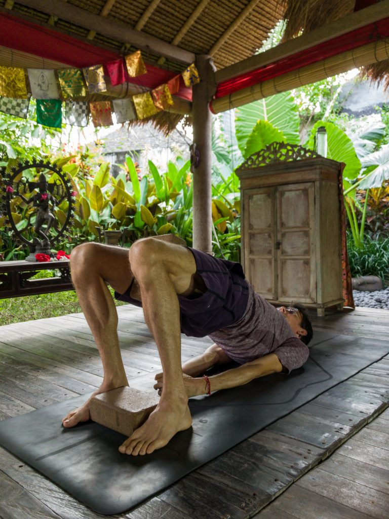 stephen doing bridge pose with yoga blocks between his feet and thighs