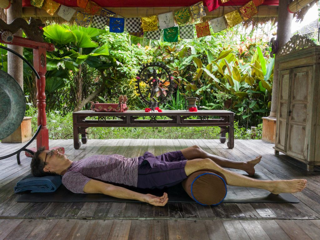 stephen doing savasana with a bolster under his knees
