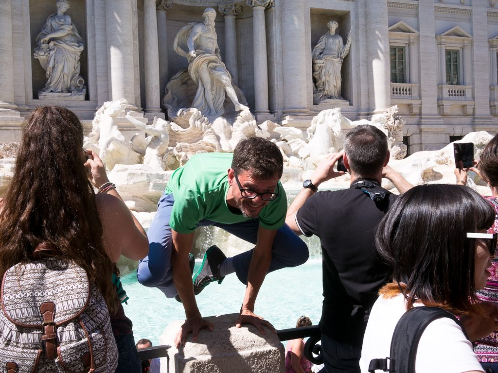 stephen doing an arm balance in front of a very crowded trevi fountain in rome