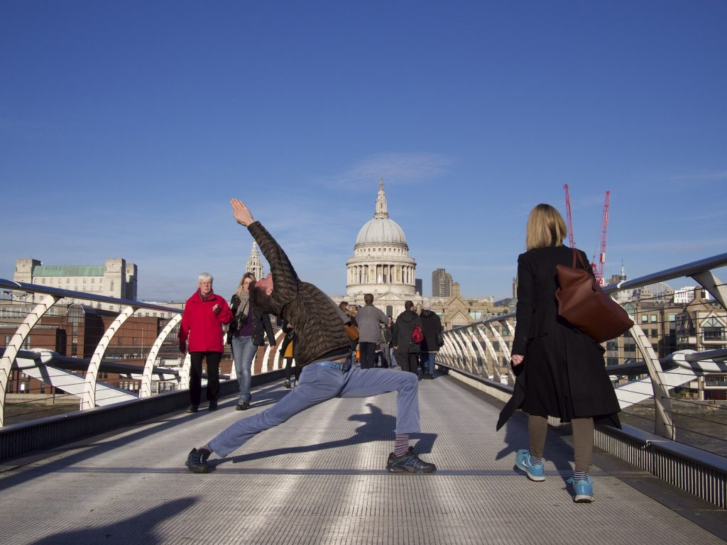 stephen doing virabhadrasana 1 on the millennium bridge in London