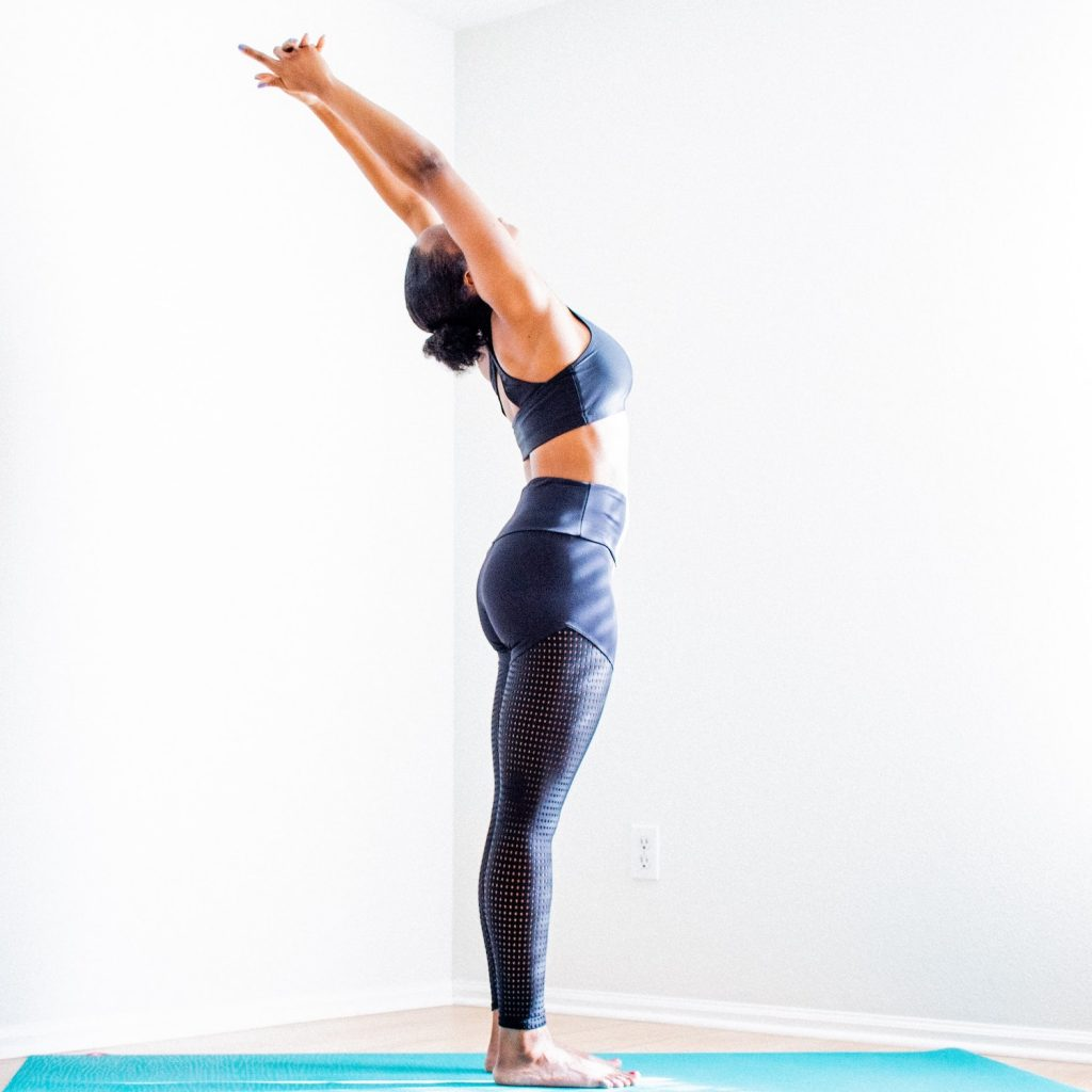 woman doing a standing back bend on a yoga mat