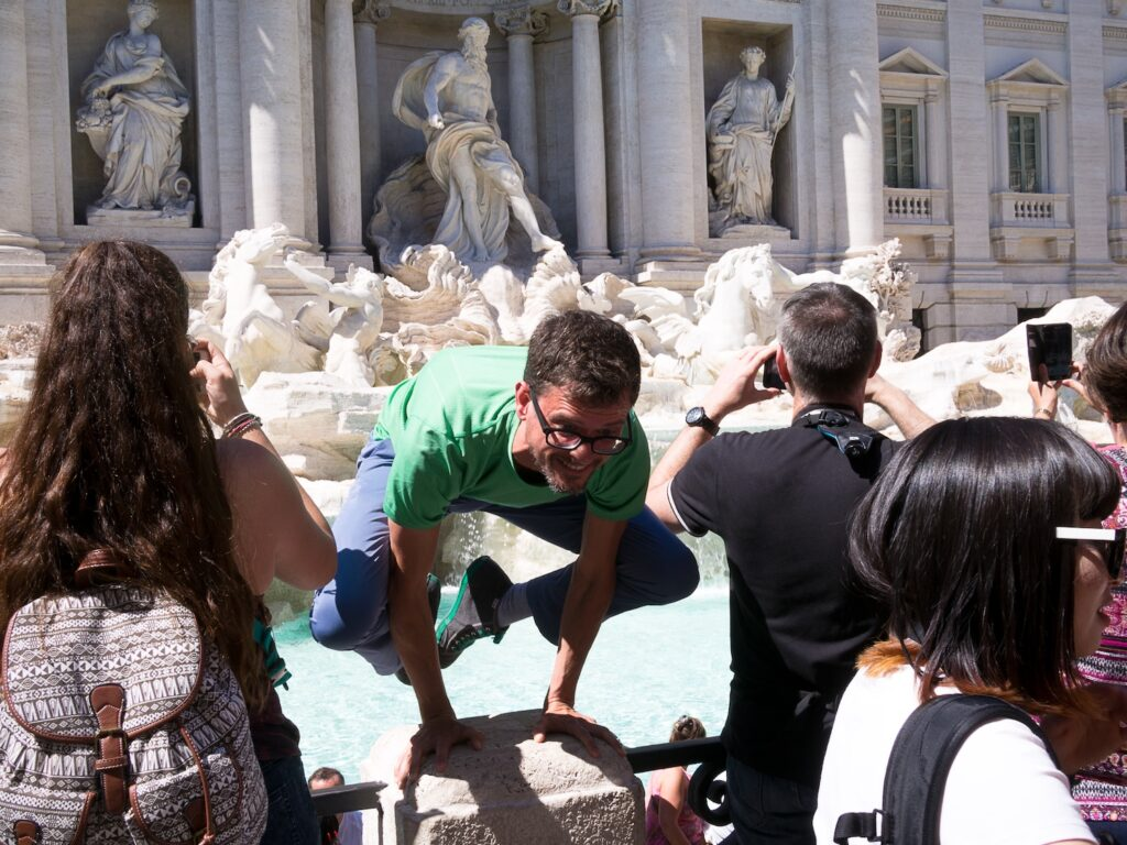 stephen doing crow pose on a pillar at the trevi fountain amid a crowd of tourists