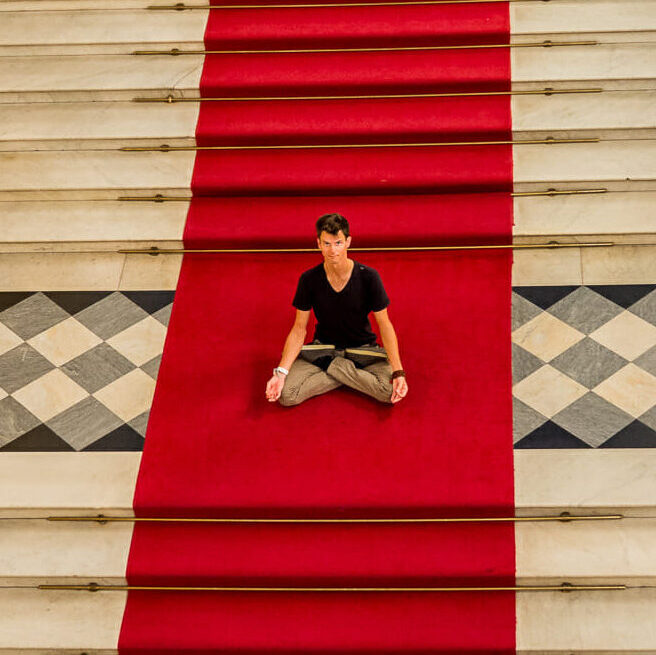 stephen doing padmasana on the stairs at the hermitage in st. petersburg