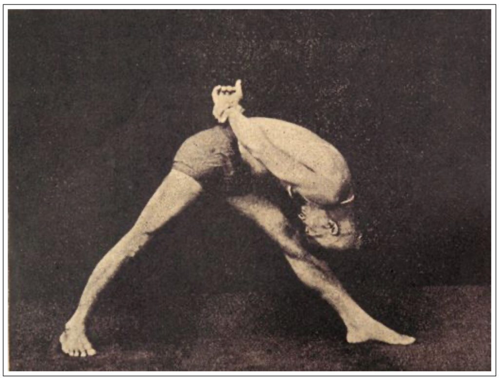 photo of Krishnamacharya in pyramid pose or parsvottanasana with his hand clasping his wrist behind his back