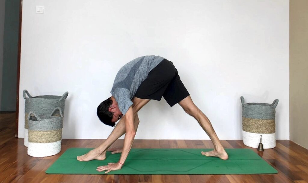 Stephen doing Parsvottanasana with hands planted on the floor.